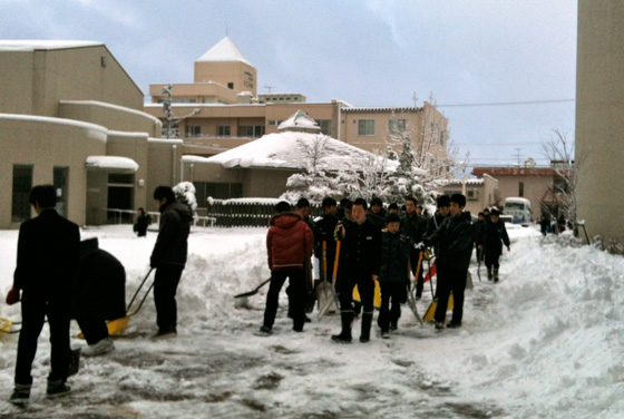 Japanese students shovel the sidewalk outside school in Toyama Prefecture
